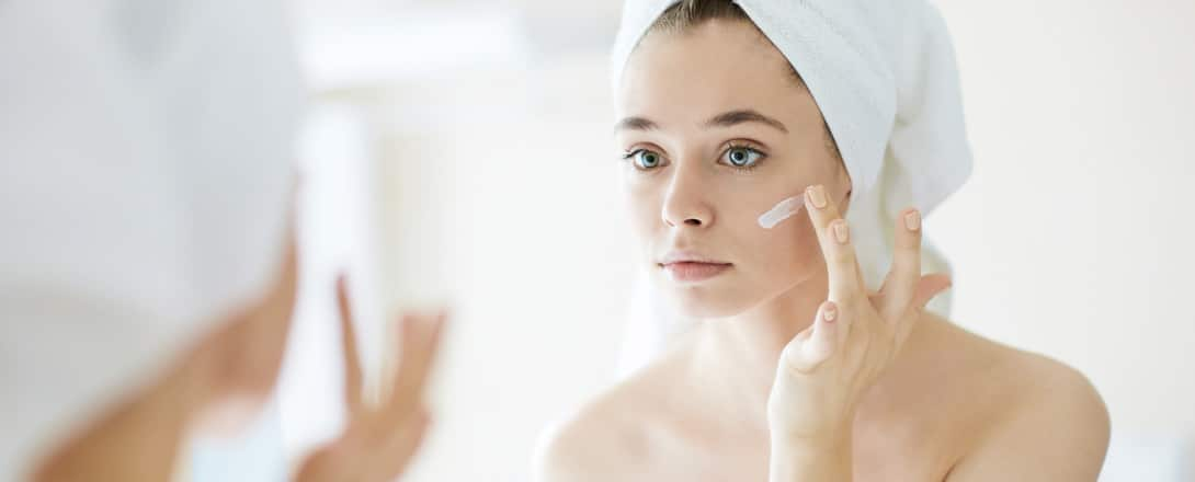 Photo of young woman applying skincare products to face while looking in the mirror.